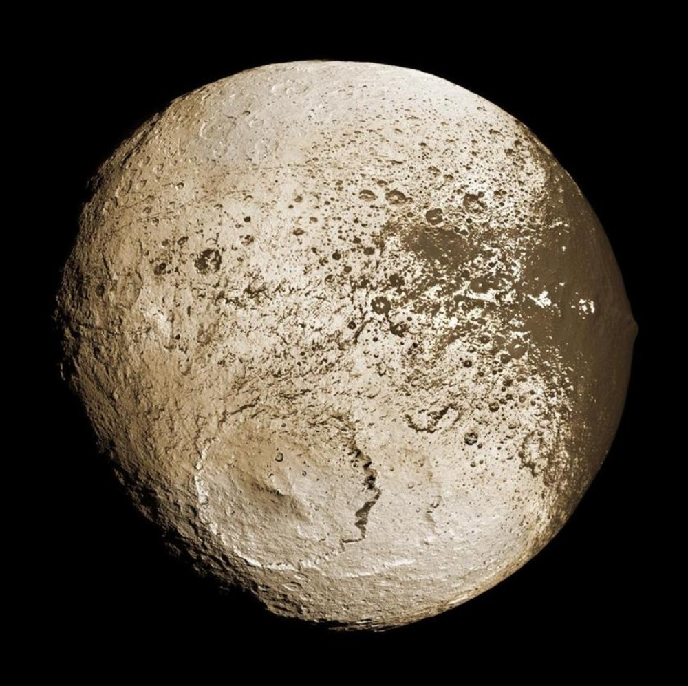 Iapetus, the third largest of the more than 60 moons of Saturn, with one side almost totally black and the other white. It is walnut-shaped, with a ridge that is about 15 kilometers high, and 50 kilometers wide