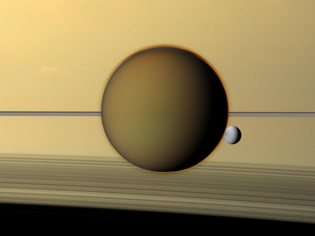 Saturn on the background with Titan and Dione in front of it